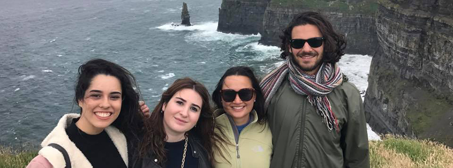 Four students posing in front of Cliffs of Moher