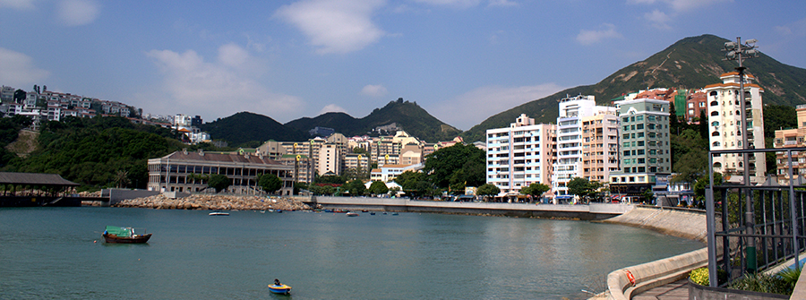 Bay with boats, buildings, and mountains