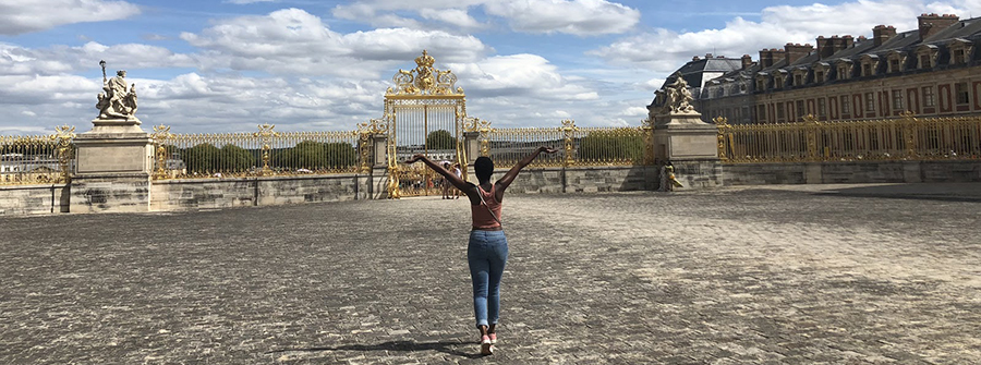 Female African-American student with arms outstretched outside Versailles