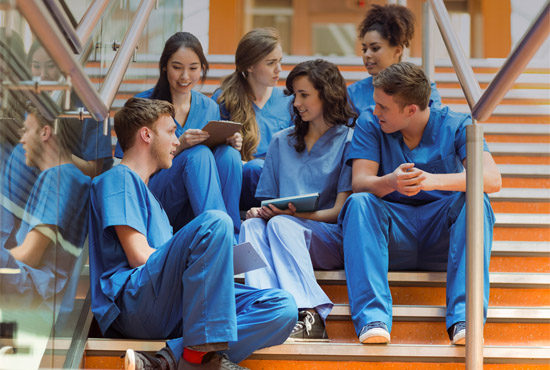 UC San Diego health / medical students in scrubs, sitting on steps